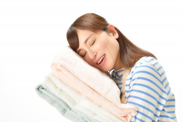 柔軟剤でふわふわになったタオルの柔らかさを実感する主婦